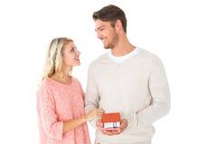 Ελκυστικό ζεύγος που κρατά το μικροσκοπικό πρότυπο σπιτιών Στοκ εικόνα με δικαίωμα ελεύθερης χρήσης