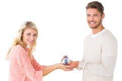 Ελκυστικό ζεύγος που κρατά το μικροσκοπικό πρότυπο σπιτιών Στοκ Εικόνες