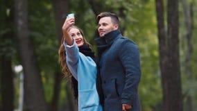 Ελκυστικό ζεύγος που φωτογραφίζεται στο πάρκο φθινοπώρου απόθεμα βίντεο