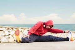 Ελκυστικό κατάλληλο τέντωμα νεαρών άνδρων πριν από την άσκηση Στοκ εικόνα με δικαίωμα ελεύθερης χρήσης