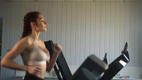 Ελκυστικό καυκάσιο κορίτσι που τρέχει treadmill στην αθλητική γυμναστική απόθεμα βίντεο