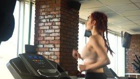 Ελκυστικό καυκάσιο κορίτσι που τρέχει treadmill στην αθλητική γυμναστική φιλμ μικρού μήκους