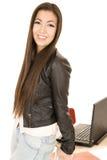 Ελκυστικό κορίτσι εφήβων που κλίνει στο γραφείο από τον υπολογιστή Στοκ Εικόνες