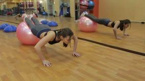 Ελκυστικό κορίτσι ικανότητας που εκτελεί την ώθηση UPS με ένα fitball στη γυμναστική απόθεμα βίντεο