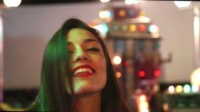 Ελκυστικό κορίτσι που χορεύει στο λούνα παρκ, που στέλνει το φιλί στη κάμερα απόθεμα βίντεο