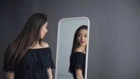 Ελκυστικό κορίτσι Brunette που κοιτάζει στον καθρέφτη απόθεμα βίντεο
