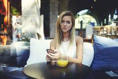Ελκυστικό κορίτσι hipster που περιμένει μια κλήση στο κινητό τηλέφωνό της απολαμβάνοντας το υπόλοιπο στο άνετο εσωτερικό καφετερι Στοκ φωτογραφία με δικαίωμα ελεύθερης χρήσης