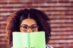 Ελκυστικό κρύψιμο χαμόγελου hipster πίσω από το βιβλίο στοκ φωτογραφία με δικαίωμα ελεύθερης χρήσης