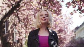 Ελκυστικό μπλε-eyed κορίτσι σε μια περιστασιακή ένδυση που περπατά κάτω από την αλέα sakura, σχετικά με την τρίχα της, χαμογελώντ απόθεμα βίντεο