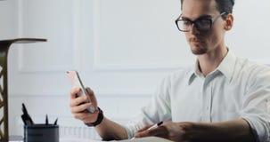 Ελκυστικό νέο επιχειρησιακό άτομο που εργάζεται στο γραφείο, που κοιτάζει στο smartphone του, φωτεινή σύγχρονη μικρή δημιουργική  απόθεμα βίντεο