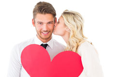 Ελκυστικό νέο ζεύγος που κρατά την κόκκινη καρδιά Στοκ Φωτογραφία