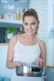 Ελκυστικό νέο μαγείρεμα γυναικών στην κουζίνα Στοκ Εικόνες