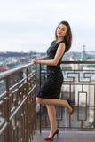 Ελκυστικό νέο όμορφο κορίτσι που φορά την κλασσική μαύρη τοποθέτηση φορεμάτων στο μπαλκόνι του κτηρίου πολυτέλειας Στοκ Εικόνα