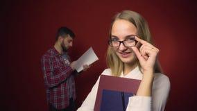 Ελκυστικό ξανθό κορίτσι σπουδαστών με τα γυαλιά στο κόκκινο φιλμ μικρού μήκους