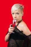 Ελκυστικό ξανθό ποτήρι εκμετάλλευσης κοριτσιών του κόκκινου κρασιού Στοκ Εικόνες