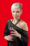 Ελκυστικό ξανθό ποτήρι εκμετάλλευσης κοριτσιών του κόκκινου κρασιού Στοκ εικόνα με δικαίωμα ελεύθερης χρήσης