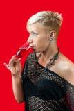 Ελκυστικό ξανθό ποτήρι εκμετάλλευσης κοριτσιών του κόκκινου κρασιού Στοκ Εικόνα