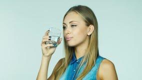 Ελκυστικό ξανθό πόσιμο νερό από ένα γυαλί σε ένα άσπρο υπόβαθρο φιλμ μικρού μήκους