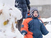 Ελκυστικό παιχνίδι αγοράκι με το πρώτο χιόνι Χαμογελά και φαίνεται χιονάνθρωπος Πυκνά μπλε-πορτοκαλής jumpsuit φωτεινός ριγωτός Στοκ Εικόνες