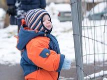 Ελκυστικό παιχνίδι αγοράκι με το πρώτο χιόνι Χαμογελά και φαίνεται χιονάνθρωπος Πυκνά μπλε-πορτοκαλής jumpsuit φωτεινός ριγωτός Στοκ εικόνες με δικαίωμα ελεύθερης χρήσης