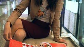 Ελκυστικό περιοδικό ανάγνωσης γυναικών στον καναπέ στο εμπορικό κέντρο φιλμ μικρού μήκους