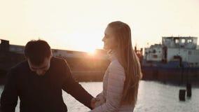 Ελκυστικό ρομαντικό ζεύγος που εξετάζει τις βάρκες στο λιμάνι στο θαλάσσιο λιμένα, που περπατά και που απολαμβάνει το όμορφο ηλιο απόθεμα βίντεο