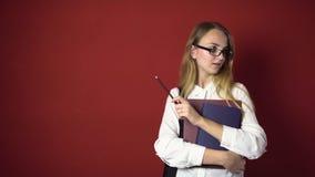 Ελκυστικό στοχαστικό ξανθό κορίτσι σπουδαστών στο κόκκινο απόθεμα βίντεο