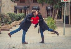 Ελκυστικό φίλημα ζευγών με ένα κόκκινο μαξιλάρι καρδιών Στοκ Φωτογραφίες