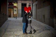 Ελκυστικό φίλημα ζευγών με ένα κόκκινο μαξιλάρι καρδιών Στοκ Εικόνα
