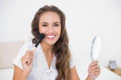 Ελκυστικό brunette χαμόγελου που κρατά μια βούρτσα και έναν καθρέφτη Στοκ φωτογραφία με δικαίωμα ελεύθερης χρήσης