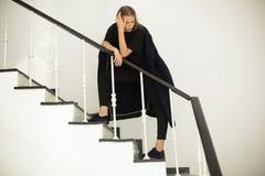 Ελκυστικό gir λ σε ένα παλτό μαλλιού που στέκεται στα σκαλοπάτια και που κοιτάζει κάτω στοκ φωτογραφία