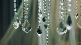 Εδροτομημένα πολύτιμους λίθους μόρια κρεμαστών κοσμημάτων πολυελαίων γυαλί στην κρεβατοκάμαρα, κρεβάτι με το πέπλο φιλμ μικρού μήκους