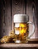 Εδροτομημένη πολύτιμους λίθους κούπα της ελαφριάς μπύρας με τον αφρό και τα αυτιά Στοκ εικόνα με δικαίωμα ελεύθερης χρήσης
