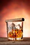 Εδροτομημένο πολύτιμους λίθους γυαλί με το ουίσκυ και το πούρο Στοκ Φωτογραφίες