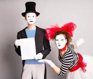εδώ κείμενό σας Κενός κενός πίνακας εκμετάλλευσης δραστών mimes Ζωηρόχρωμο πορτρέτο στούντιο με το γκρίζο υπόβαθρο ενάντια στον μ Στοκ Εικόνα