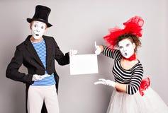 εδώ κείμενό σας Κενός κενός πίνακας εκμετάλλευσης δραστών mimes Ζωηρόχρωμο πορτρέτο στούντιο με το γκρίζο υπόβαθρο ενάντια στον μ Στοκ Εικόνες