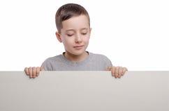 εδώ κείμενό σας Το αγόρι στέκεται κοντά στον κενό κενό πίνακα και κοιτάζει Στοκ Φωτογραφίες