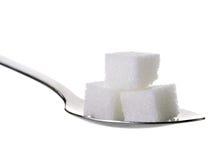 Ζάχαρες κύβων στο κουταλάκι του γλυκού στο άσπρο υπόβαθρο Στοκ Φωτογραφίες