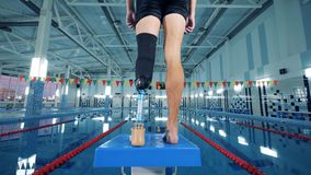Ζέσταμα ενός ατόμου με ένα ρομποτικό πόδι πρίν πηδά στην πισίνα φιλμ μικρού μήκους