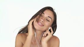 Ζαλίζοντας γυναίκα με βαθιά - τα πράσινα μάτια και μακρυμάλλης ακούνε τη μουσική που στέκεται ενάντια στον αέρα φιλμ μικρού μήκους