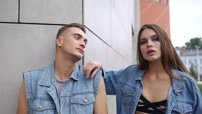 Ζαλίζοντας γυναίκα με τις μακρυμάλλεις στάσεις πίσω από έναν άνδρα στην τοποθέτηση σακακιών τζιν πριν από έναν γκρίζο τοίχο φιλμ μικρού μήκους