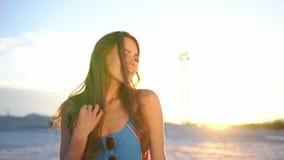 Ζαλίζοντας γυναίκα brunette με τους μακρυμάλλεις χορούς στα φω'τα βραδιού στην παραλία απόθεμα βίντεο