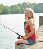 Ζαλίζοντας νέα ξανθή αλιεία γυναικών από την αποβάθρα Στοκ Εικόνα