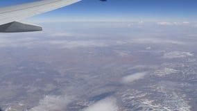 Ζαλίζοντας ομορφιά της σειράς βουνών, που καλύπτεται ελαφρώς με το χιόνι, που περνά από τα σύννεφα, μια άποψη από το παράθυρο αερ απόθεμα βίντεο