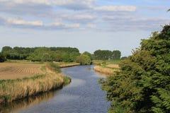 Ζαλίζοντας πανοραμική άποψη στους τομείς σε μια ηλιόλουστη ημέρα με ένα κανάλι και τα δέντρα Στοκ Φωτογραφία