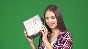 Ζαλίζοντας την ευτυχή νέα γυναίκα που τινάζει το παρόν κιβώτιο που υποθέτει τι είναι μέσα απόθεμα βίντεο