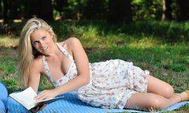 Ζαλίζοντας τη νέα ξανθή γυναίκα στα sundress - ανάγνωση Στοκ Εικόνες