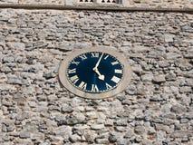 Ζαλίζοντας το παλαιό ρολόι έξω στο τουβλότοιχο εκκλησιών Στοκ Εικόνες