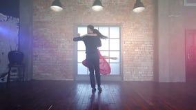 Ζαλίζοντας χορεύοντας λατινικά ζευγών σε ένα σύγχρονο στούντιο στον καπνό φιλμ μικρού μήκους