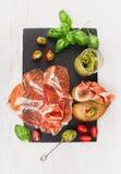 Ζαμπόν Prosciutto με το ψωμί, το pesto βασιλικού και τις ντομάτες στην πλάκα Στοκ φωτογραφία με δικαίωμα ελεύθερης χρήσης